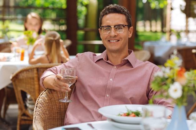 Homem sorridente. homem sorridente usando óculos e sentindo-se bastante aliviado ao se comunicar com seu amigo