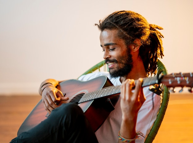 Homem sorridente lateralmente com dreads tocando guitarra