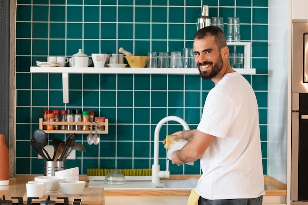 Homem sorridente lavando prato tiro médio