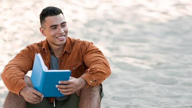 Homem sorridente lendo livro na praia com espaço de cópia