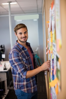 Homem sorridente lendo post-its no quadro no escritório