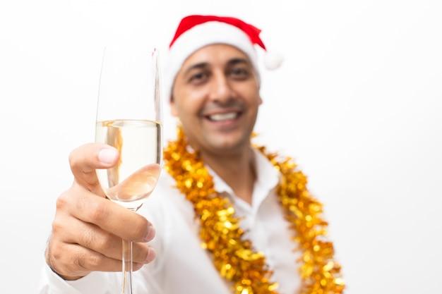 Homem sorridente levantando vidro com champanhe