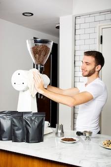 Homem sorridente, limpando a máquina de café