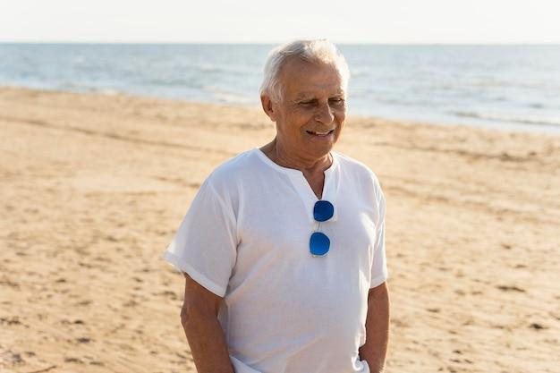 Homem sorridente mais velho aproveitando o tempo na praia