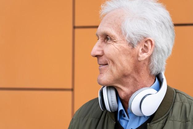 Homem sorridente mais velho na cidade com fones de ouvido