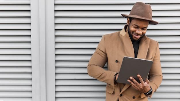 Homem sorridente moderno olhando em seu tablet