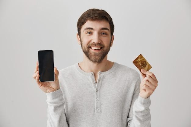 Homem sorridente, mostrando a tela do smartphone e o cartão de crédito. comprar online