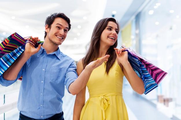 Homem sorridente mostrando algo de mulher no shopping