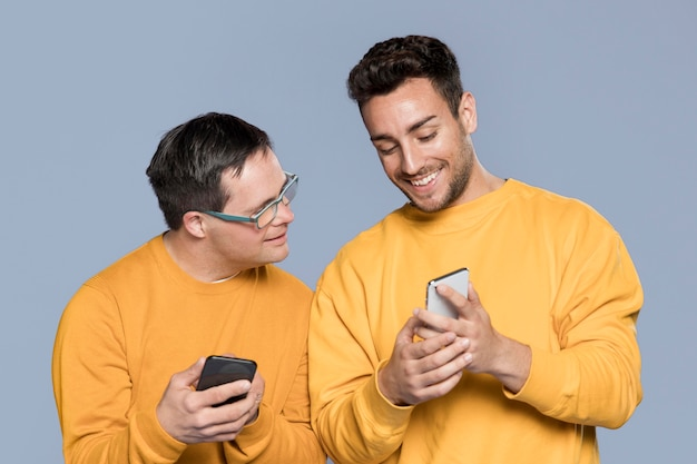 Homem sorridente, mostrando algo para seu amigo no telefone