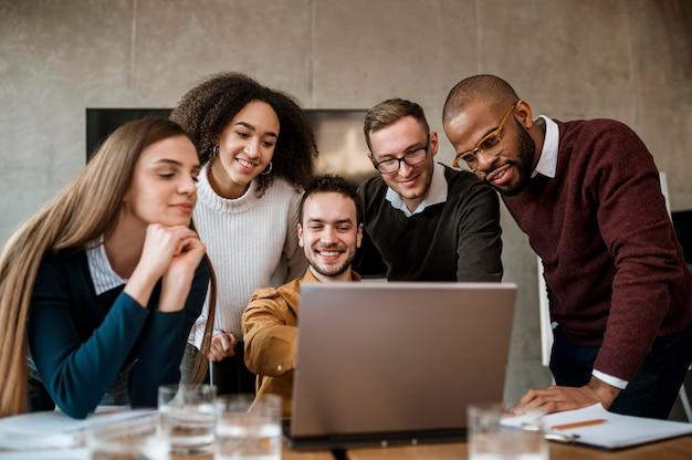 Homem sorridente mostrando algo para seus colegas no laptop durante uma reunião