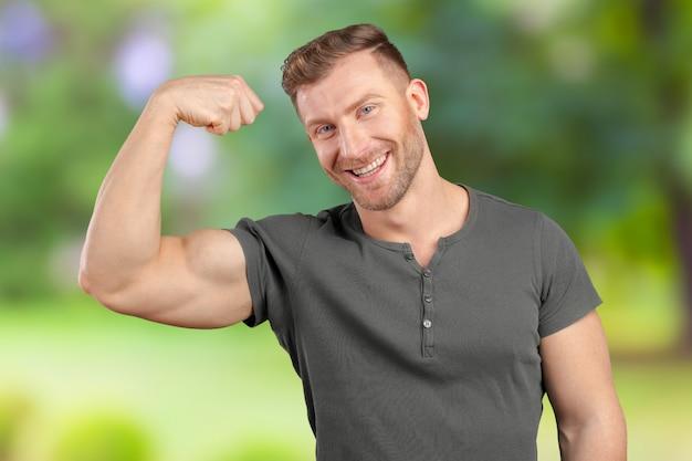 Homem sorridente, mostrando o bíceps