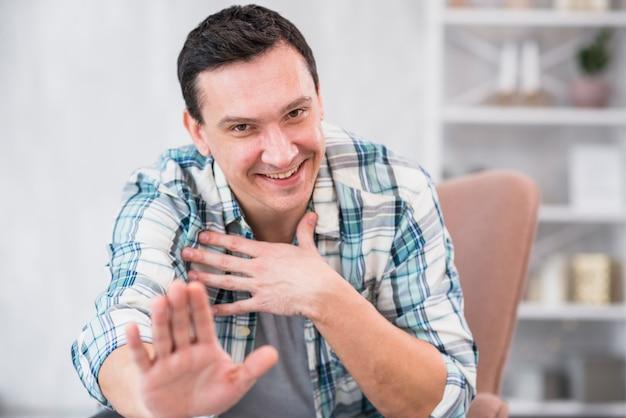 Homem sorridente, mostrando o gesto de parada na cadeira em casa