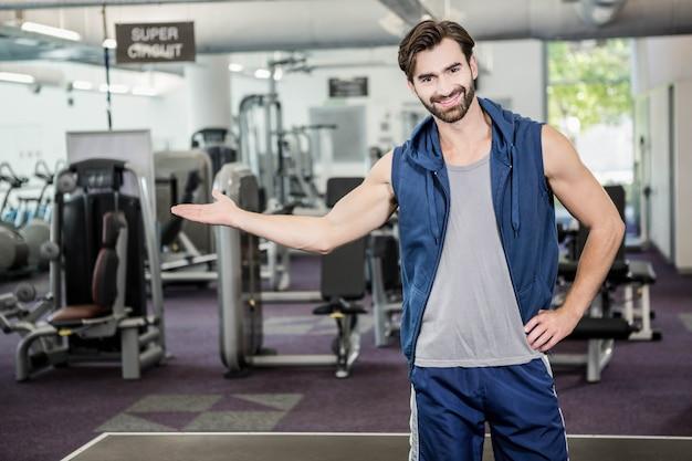 Homem sorridente, mostrando o ginásio para a câmera