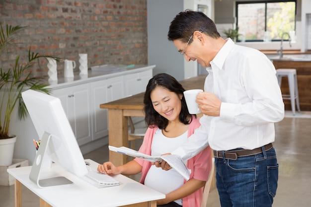 Homem sorridente, mostrando o jornal para sua esposa grávida em casa