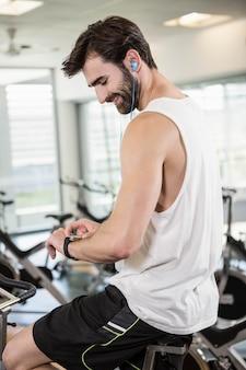 Homem sorridente na bicicleta ergométrica usando smartwatch no ginásio
