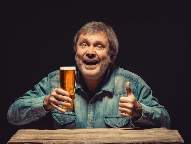 Homem sorridente na camisa jeans com copo de cerveja