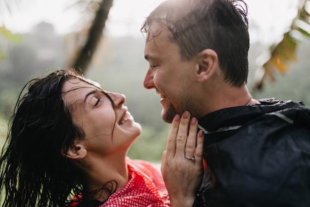 Homem sorridente na capa de chuva, olhando com amor para uma mulher morena. rindo casal romântico dançando na natureza.
