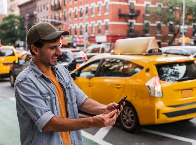 Homem sorridente na cidade segurando móvel