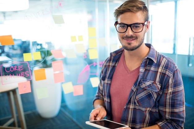 Homem sorridente no escritório usando tablet digital contra notas adesivas na parede