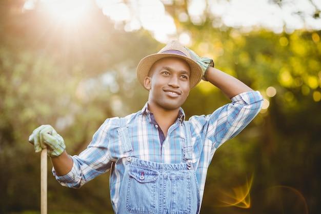 Homem sorridente no jardim a desviar o olhar