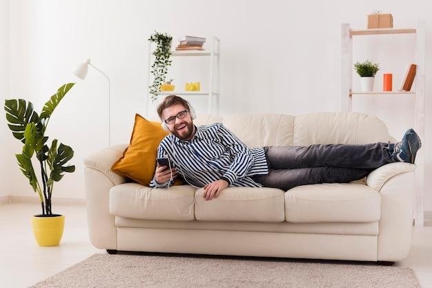 Homem sorridente no sofá a gostar de música