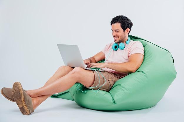Homem sorridente no sofá segurando laptop