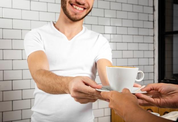 Homem sorridente, oferecendo uma xícara de café