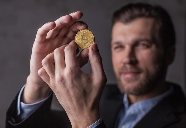 Homem sorridente olha bitcoin em suas mãos. foco na moeda