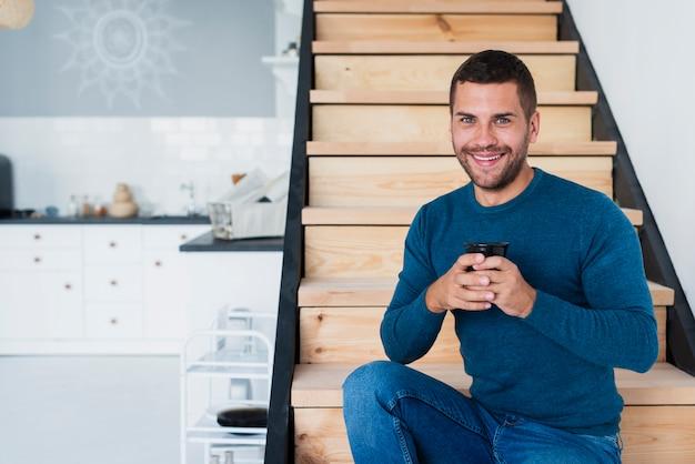Homem sorridente, olhando para a câmera e segurando uma xícara de café