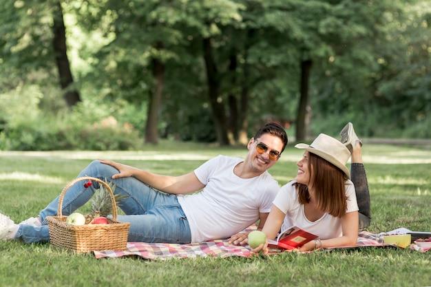 Homem sorridente, olhando para a namorada no piquenique