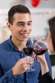 Homem sorridente, olhando para a namorada, segurando um copo de vinho