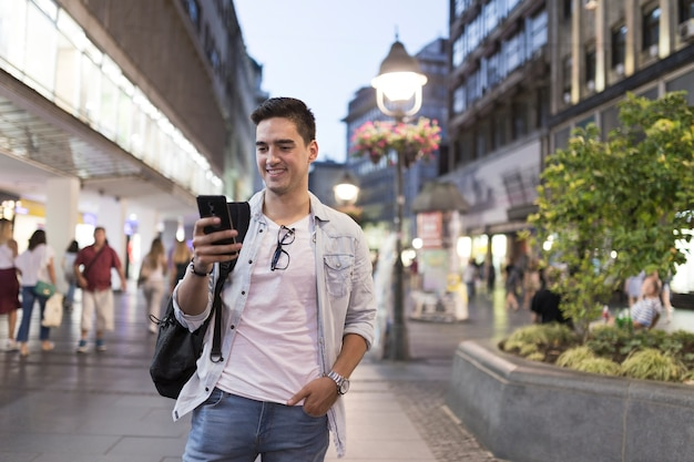 Homem sorridente, olhando para a tela do telefone móvel