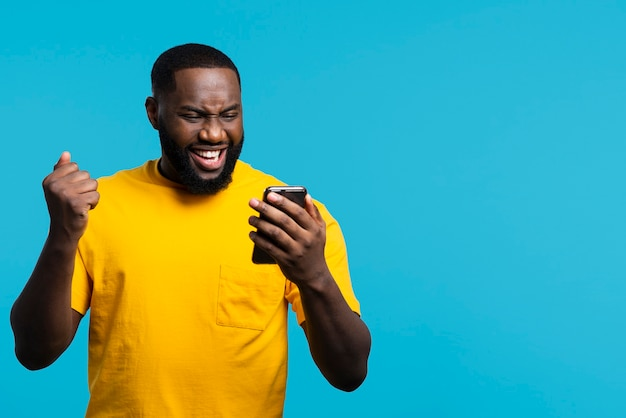 Homem sorridente, olhando para o celular