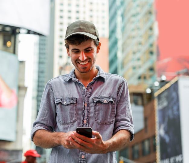 Homem sorridente, olhando para o smartphone