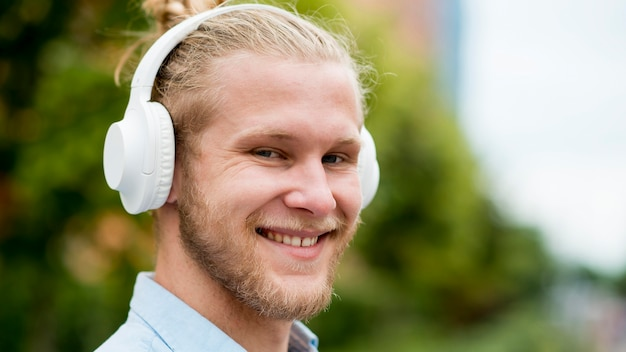 Homem sorridente, ouvindo música em fones de ouvido