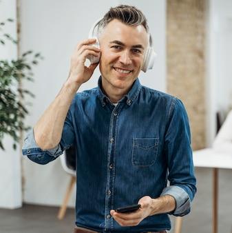 Homem sorridente ouvindo música em uma reunião