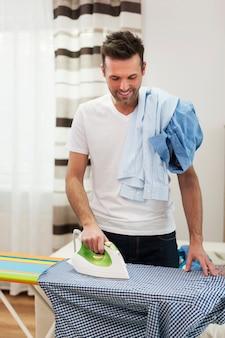 Homem sorridente passando suas camisas
