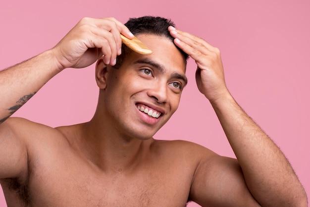 Homem sorridente penteando o cabelo