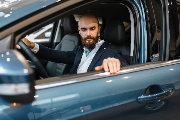 Homem sorridente posa em automóvel novo na concessionária. cliente no showroom de veículos, homem comprando transporte, concessionária de automóveis