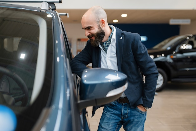 Homem sorridente posa para automóvel na concessionária. cliente em showroom de veículos novos, homem comprando transporte, concessionária de automóveis