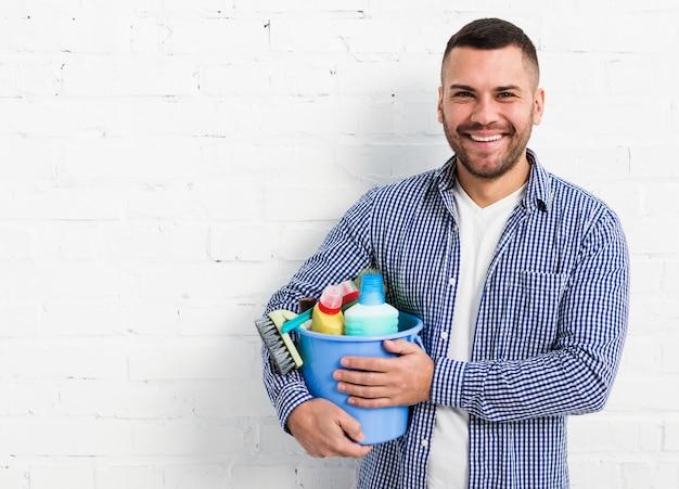 Homem sorridente posando com produtos de limpeza e cópia espaço