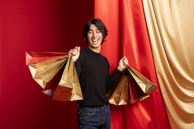 Homem sorridente posando com sacolas de compras para o ano novo chinês