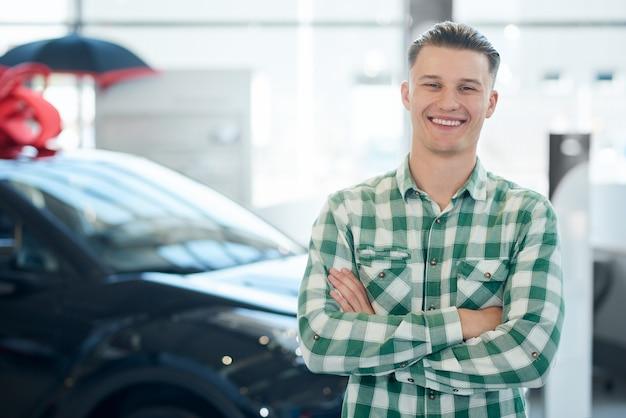 Homem sorridente posando perto de carro.