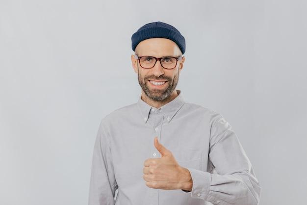 Homem sorridente positivo com barba por fazer, levanta o polegar, demonstra seu gosto