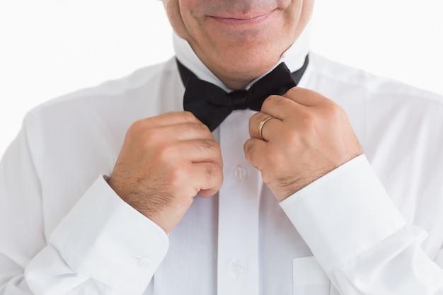 Homem sorridente que repara a gravata