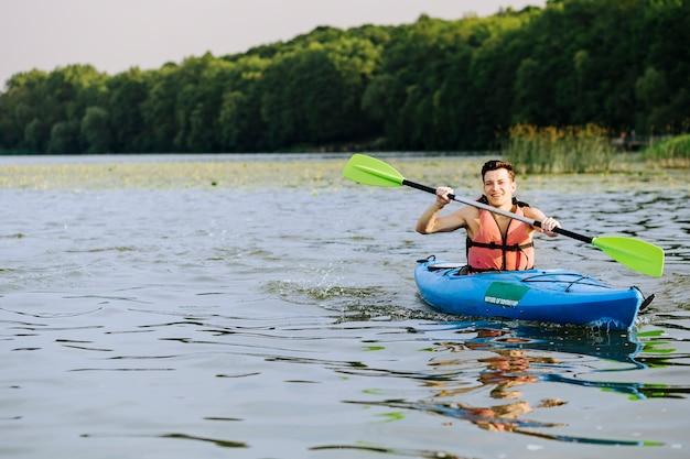 Homem sorridente salpicos de água enquanto remar o caiaque no lago