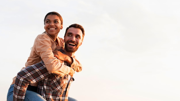 Homem sorridente segurando a namorada nas costas com espaço de cópia