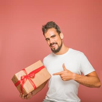 Homem sorridente, segurando, caixa presente, dedo apontando, contra, colorido, fundo