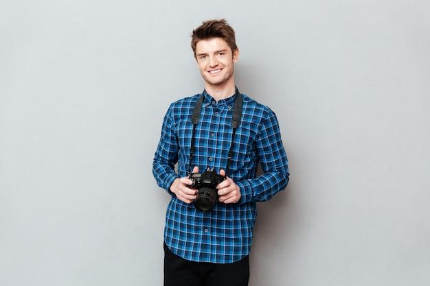 Homem sorridente, segurando câmera, em, mãos