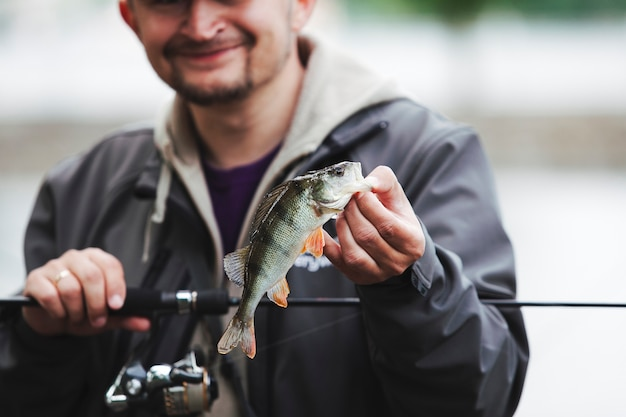 Homem sorridente, segurando, cana de pesca, mostrando, pegado, peixe